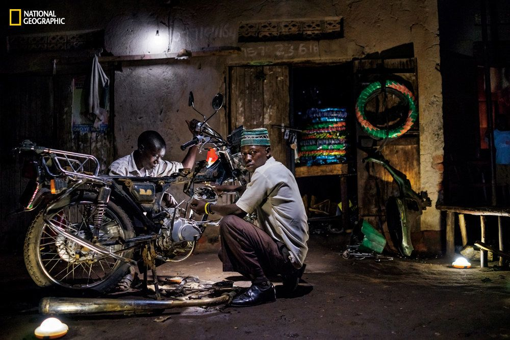 Ibrahim Kalungi and Godfrey Mteza, both 20, work at night in their motorcycle repair shop in Nbeeda, Uganda. The mechanics credit solar lights with enabling them to work longer hours and earn more money.