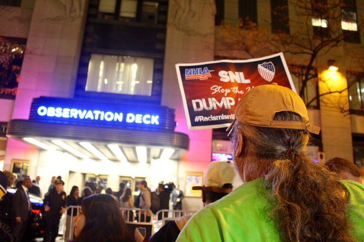 """A protester holds a sign reading """"SNL stop the hate"""" in front of the entrance to NBC headquarters at 30 Rockefeller Center on Wednesday."""