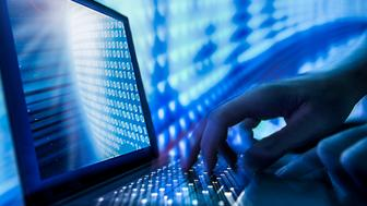 Close-up man's hands typing on laptop during cyber attack.