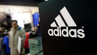 The Adidas AG logo is displayed as customers browse products at the company's store in Beijing, China, on Saturday, Feb. 18, 2012. Adidas is expected to annouce earnings on March 7. Photographer: Nelson Ching/Bloomberg via Getty Images