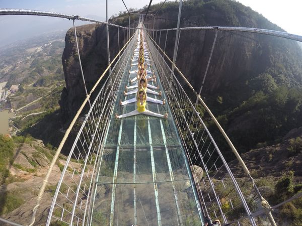 100 yoga enthusiasts practice on a glass suspension bridge at the Shiniuzhai National Geological Park on Nov. 5, 2015 in Ping