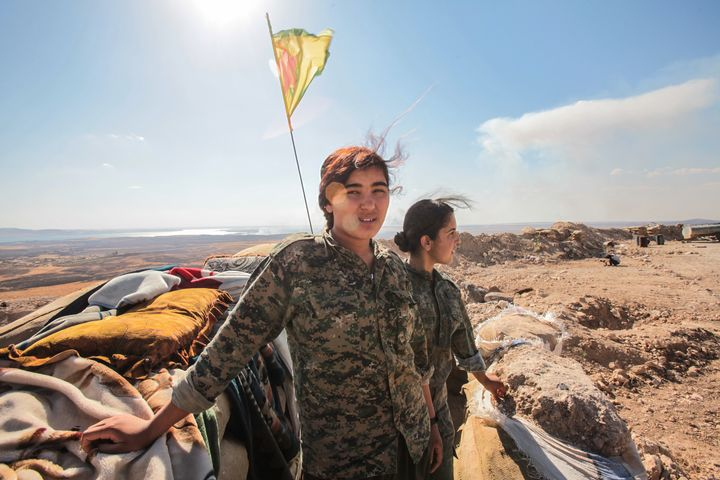 YPG fighters pose as they stand near a checkpoint in the outskirts of the destroyed Syrian town of Kobane on June 20.