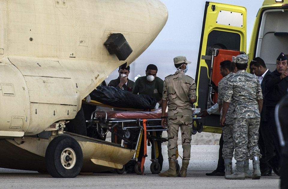 Egyptian paramedics load the corpses of the plane crash victims into a military plane at Kabret military air base, Egypt, on