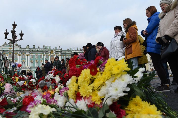 People stand next to a memorial in central St. Petersburg.