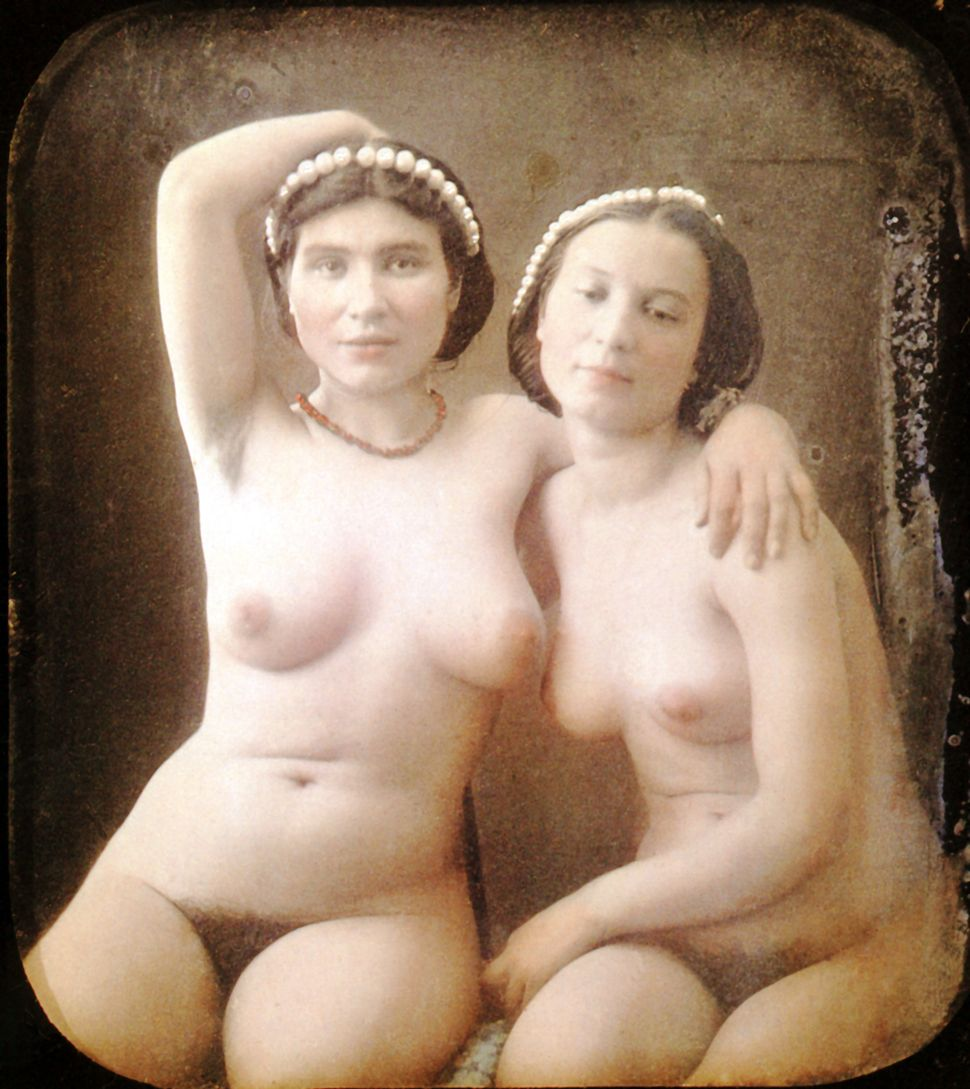 Two nude women are sitting next to one another only wearing a necklace and a string of pearl in their hair. Hand-colored ster