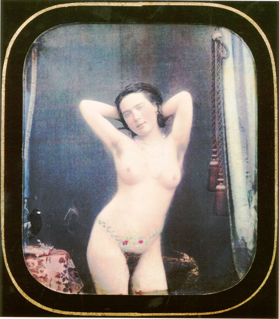 A nude woman is standing near a table with leaves and flowers painted around her waist. Hand-colored stereoscopic daguerreoty