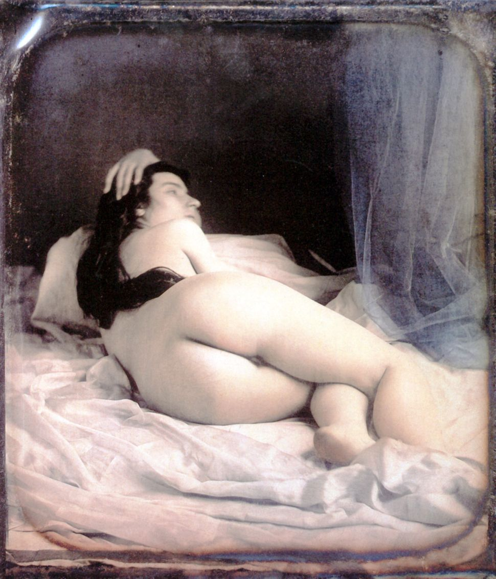 A nude woman is lying on her bed showing her back. Hand-colored stereoscopic daguerreotype. 1850.