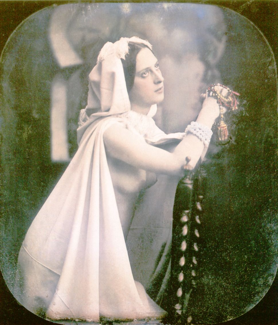 A woman is kneeling on a chair praying. She is wearing a white wedding dress which is open in the front showing her breasts.