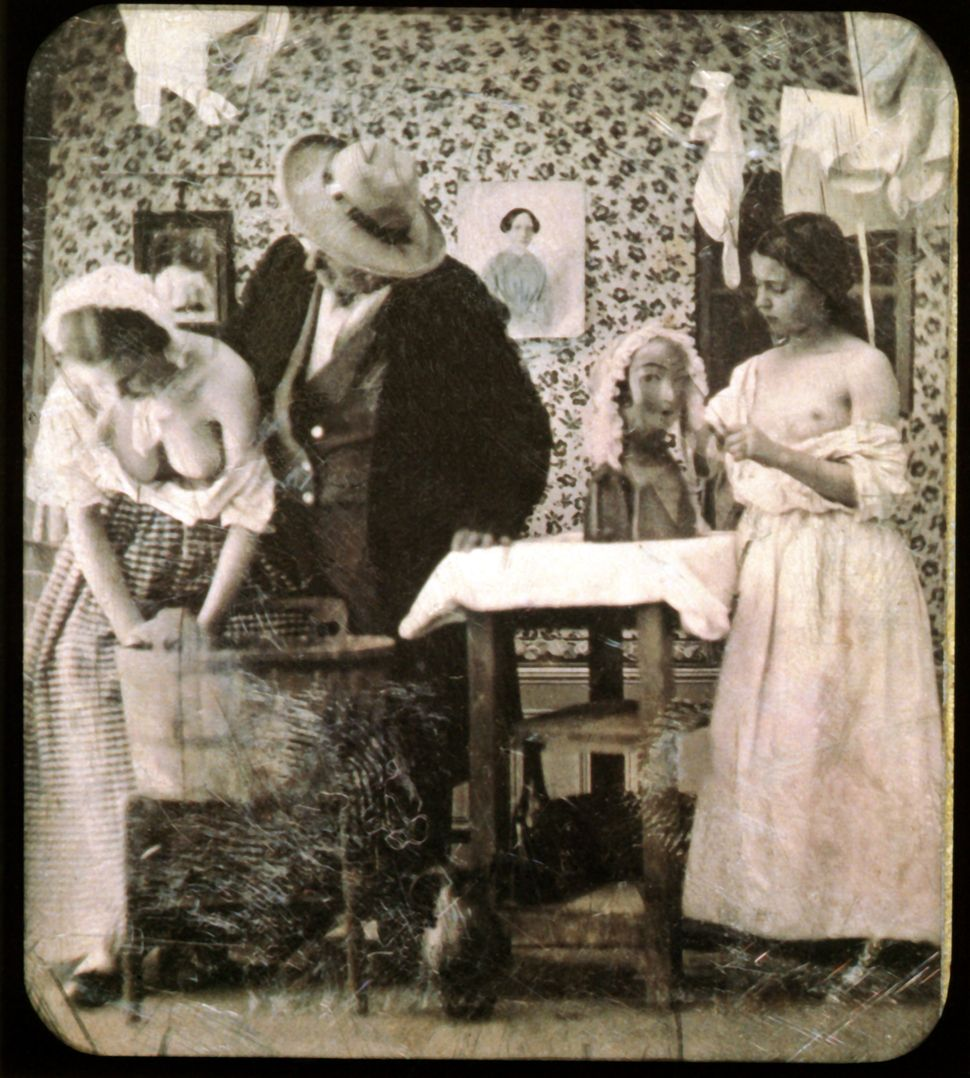Two women are taking care of laundry while an old man is standing behind one of them who has her breasts exposed while she is