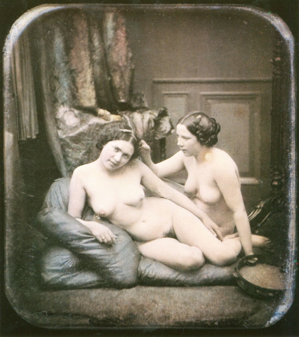 Two nude women are sitting next to one another on some cushions on the floor. Hand-colored stereoscopic daguerreotype. 1850.