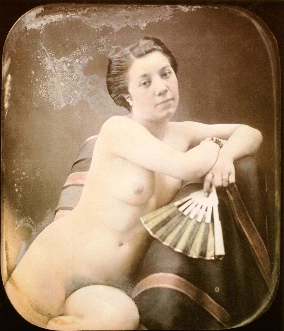 A nude woman a holding a fan is sitting in an armchair. Hand-colored stereoscopic daguerreotype. 1850.