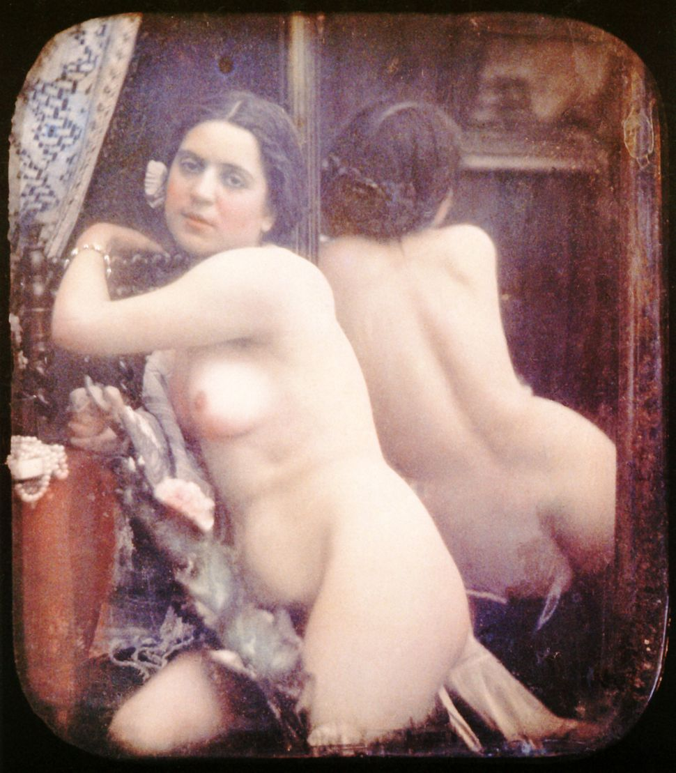 A nude woman is sitting in front of a mirror wearing a necklace. Another one (pearl) is in front of her. 1850. Hand-colored s