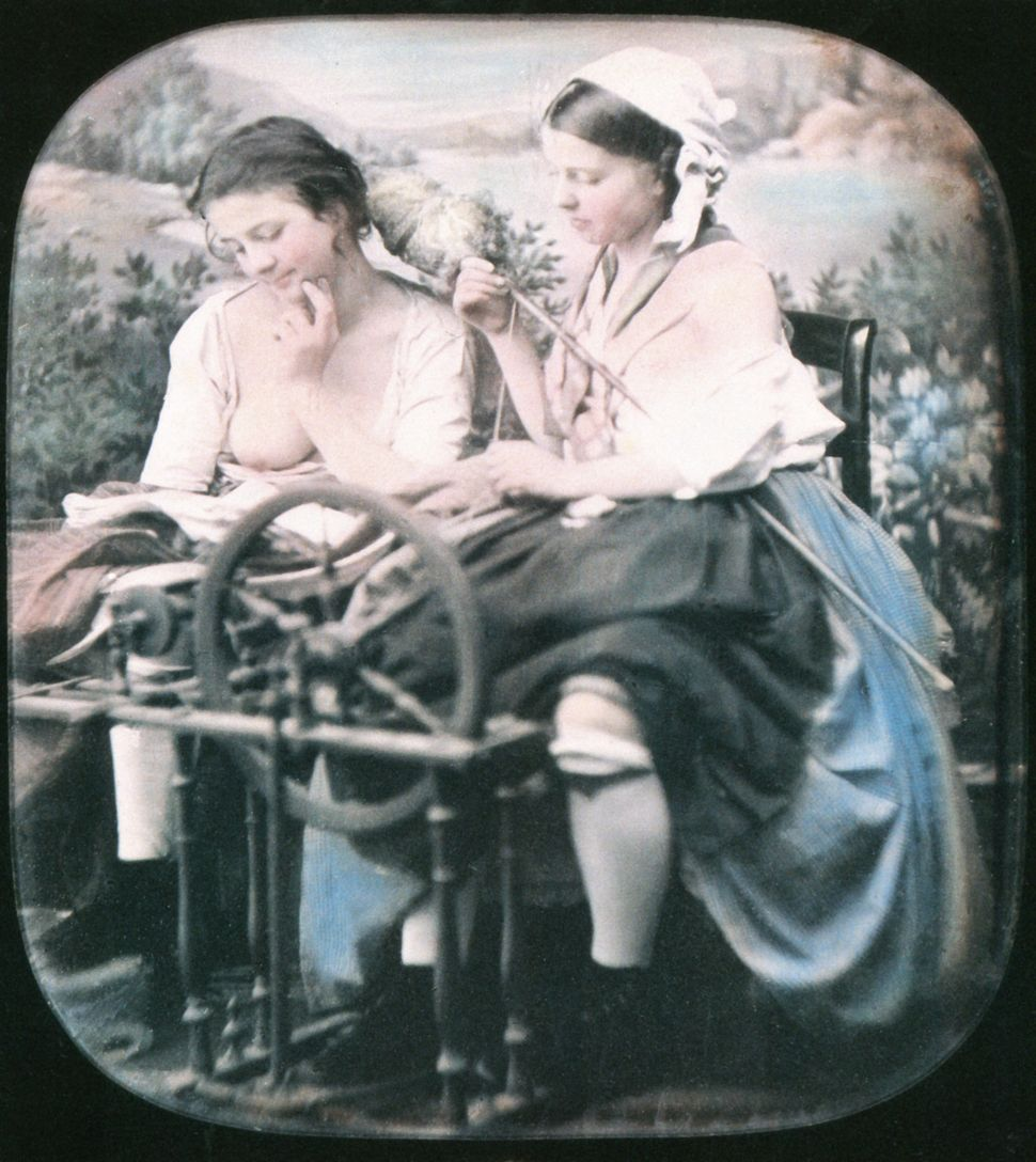 Two women are sitting next to another spinning in front of a studio curtain with countryside scenery. One has her blouse unbu