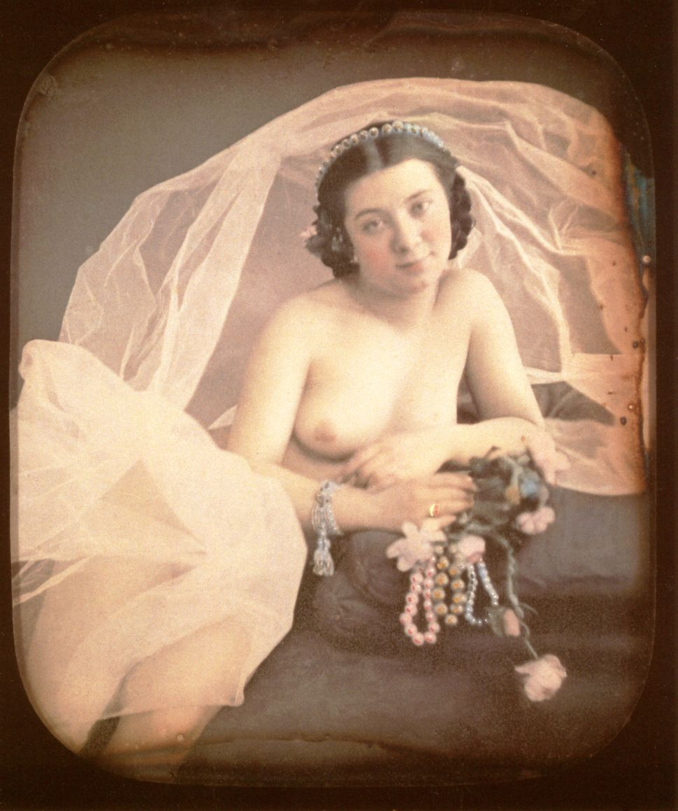 A nude woman is resting on a chaiseloungeholding pink flowers and a string of pearl with her right hand. A large