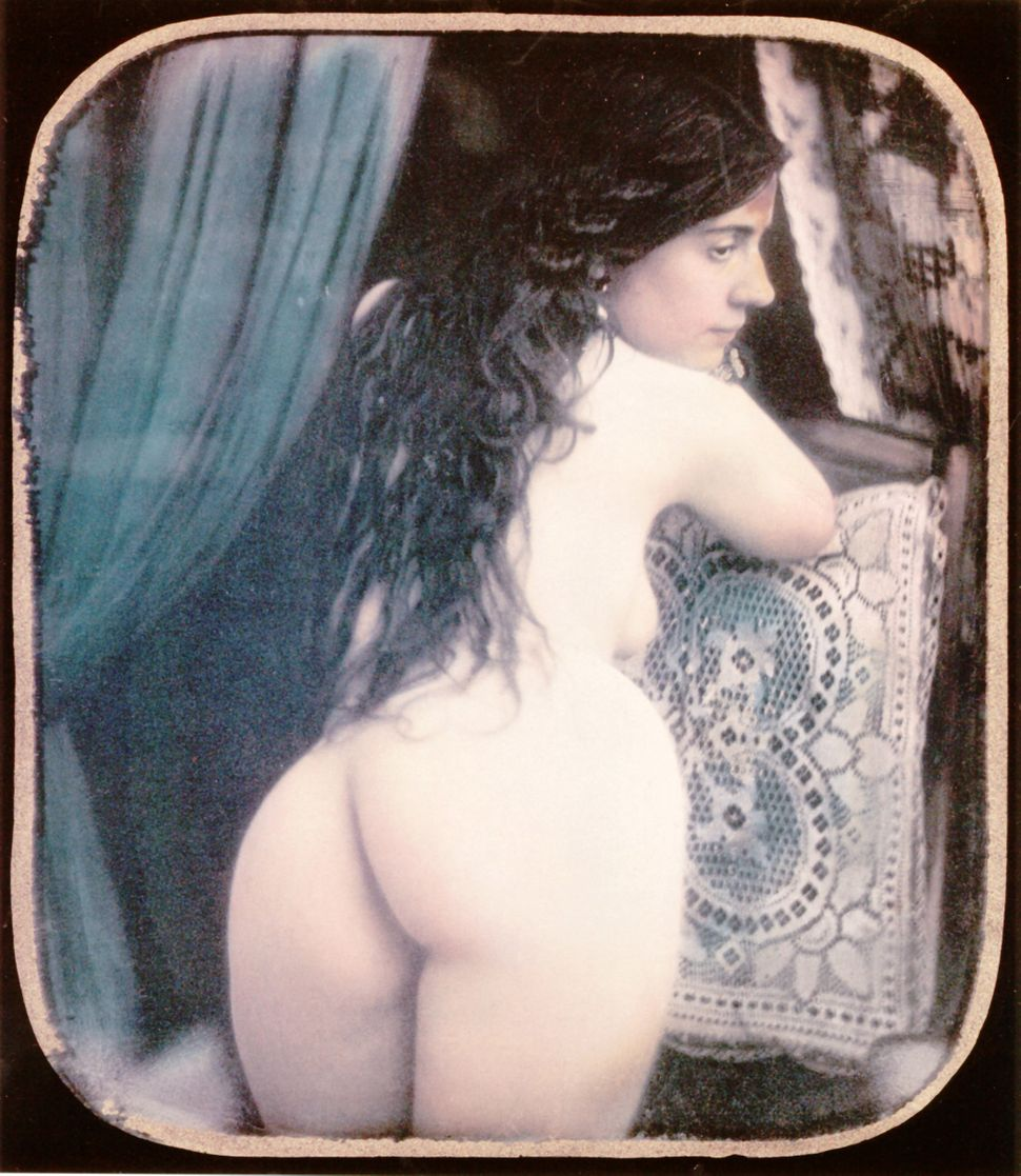 A nude woman is kneeling on a chair showing her back. Hand-colored stereoscopic daguerreotype. 1850.