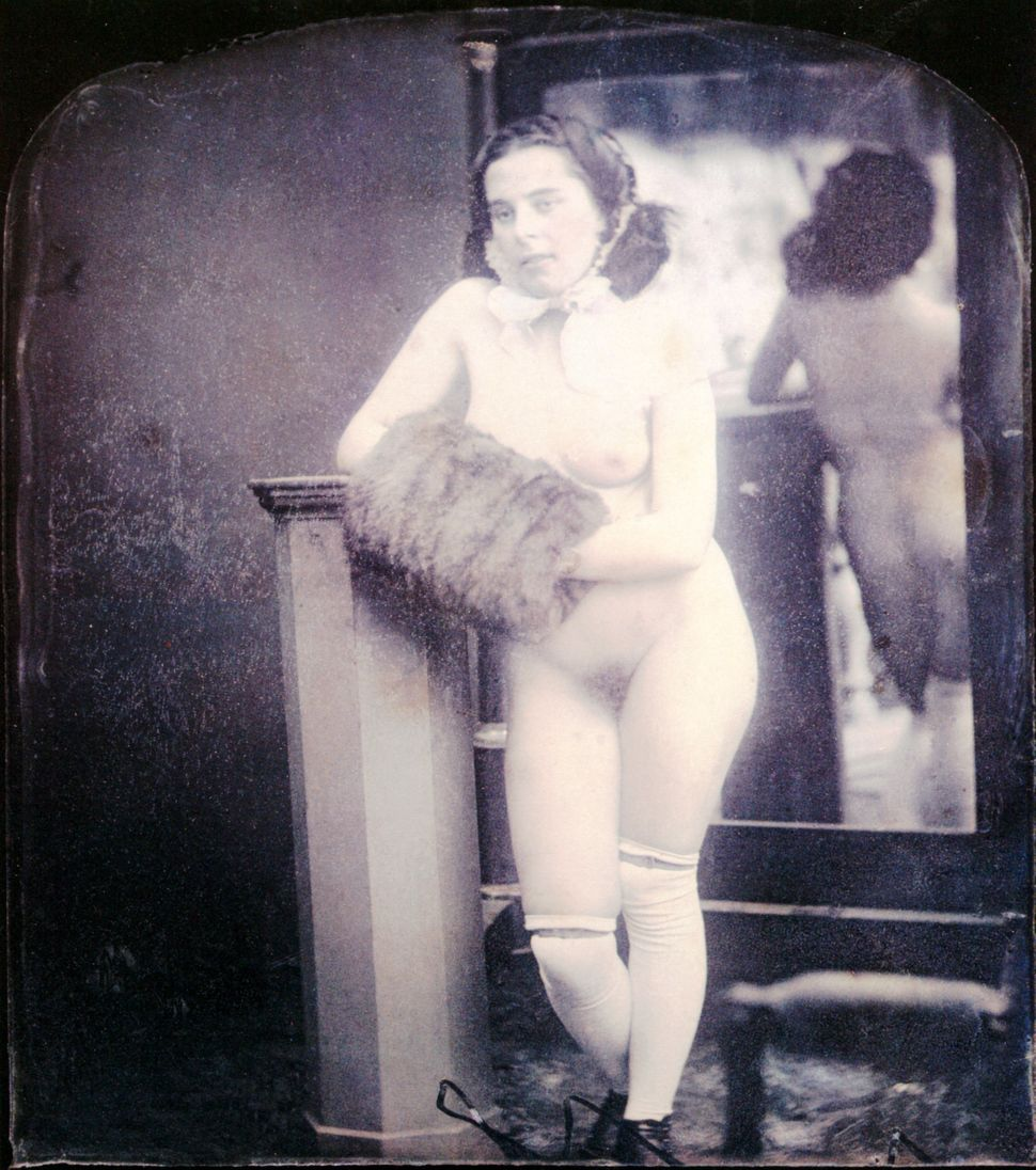 A nude woman is standing in front of a mirror wearing shoes, stockings and a hair band. Her hands are in a muff. Hand-colored