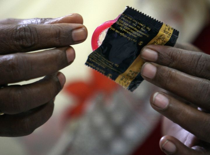 An Indian sex worker demonstrates how to use a condom during a behavioural change communication (BCC) session at the Social A