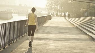 Female runner walking along river