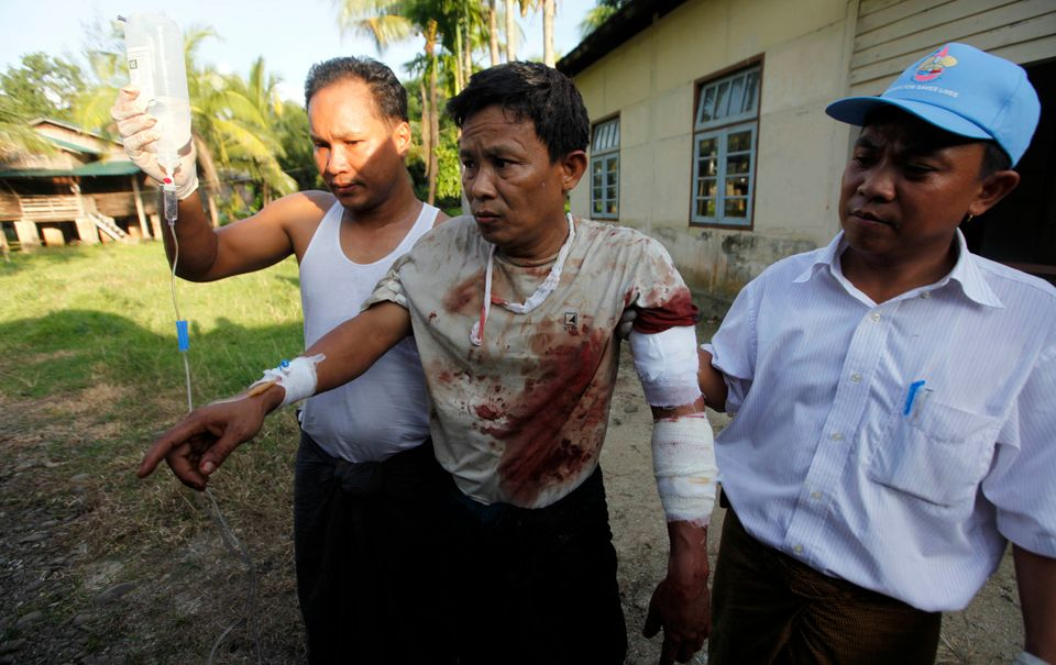In this Tuesday, Oct. 1, 2013 photo, an injured Rakhine Man, centre, is helped to go to hospital in Thandwe, Rakhine State, w