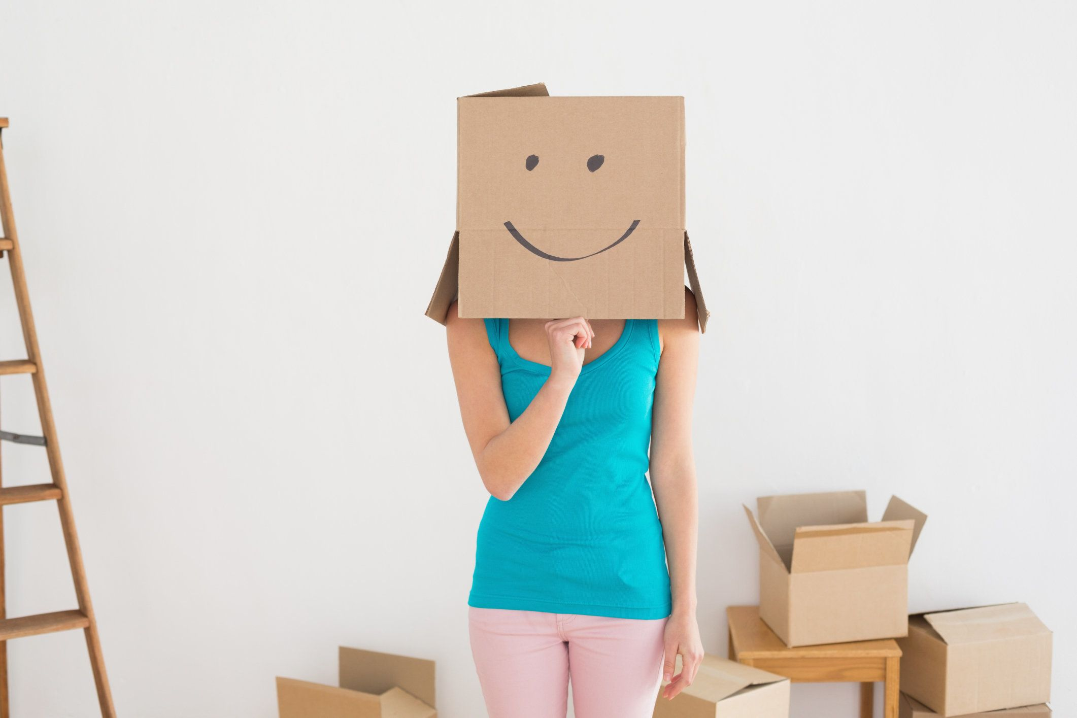 Woman in blue tank top with smiley cardboard box over face