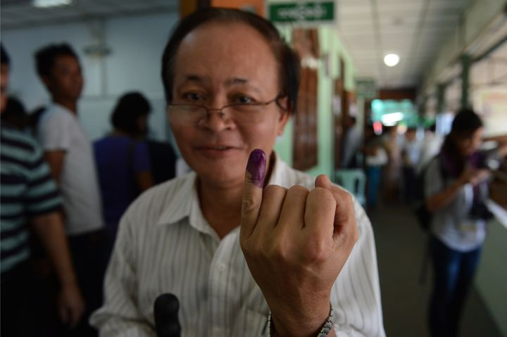 A Myanmar voter displays his inked finger after casting his ballot at a polling center in Yangon on November 8, 2015.