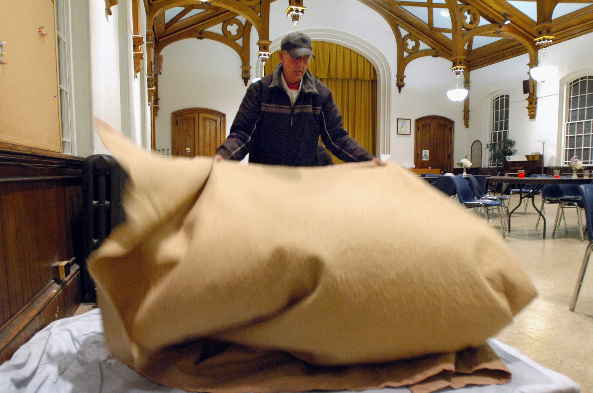 PROVIDENCE, RI - MAY 23:  Richard Golden prepares to sleep at a temporary homeless shelter at Beneficent Congregational Church in Providence, Rhode Island, on May 23, 2005. Rhode Island churches have programs for homeless people, offering meals and a spot on the floor to sleep. (Photo by John Nordell/The Christian Science Monitor via Getty Images)