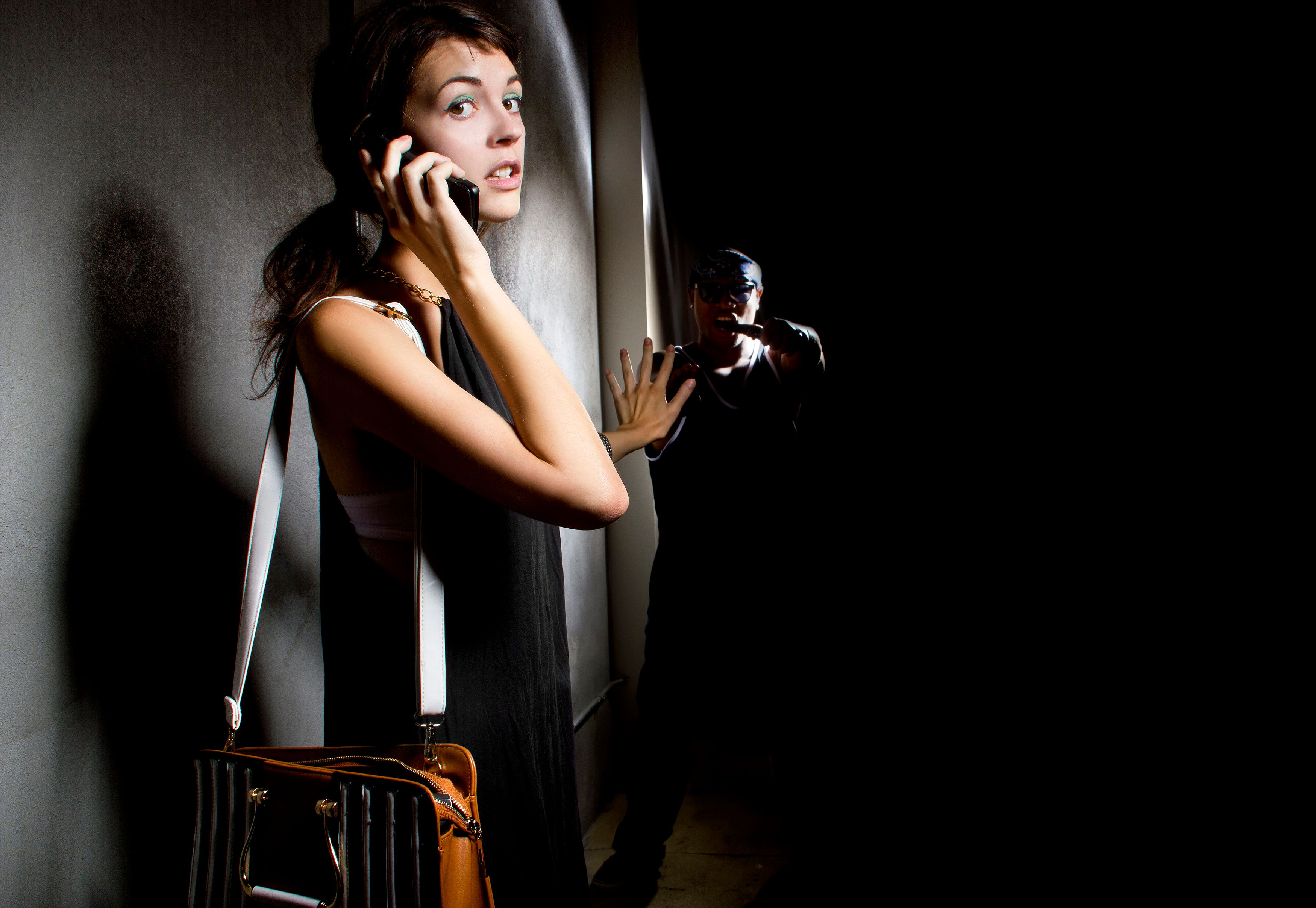 Photo of a woman calling 911 for help in an alley.  A criminal is hiding in the shadows of the street and stalking her.  The man is a robber or mugger, The female is holding a cell phone and calling the police. The image depicts crime and security.