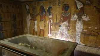 The sarcophagus of King Tutankhamun, known as the 'Child Pharaoh' remains empty in its burial chamber after the mummy was placed in a glass urn designed to protect the remains of the ancient king from humidity and other contamination brought by a constant flow of over 350 visitors a day in his tomb in the Valley of the Kings, close to Luxor, 500 kms south of Cairo 04 November 2007. Temperature will be controlled to 25 centigrade and humidity maintained around 35 percent. Tutankhamun ascended to the throne at nine years old and died at about eighteen years of age. This is the first time his uncovered face will be presented to the public 30 centuries after his death. The tomb was discovered by British collector Lord George Carnarvon and archaeologist Howard Carter 04 November 1922. AFP PHOTO/CRIS BOURONCLE        (Photo credit should read CRIS BOURONCLE/AFP/GettyImages)