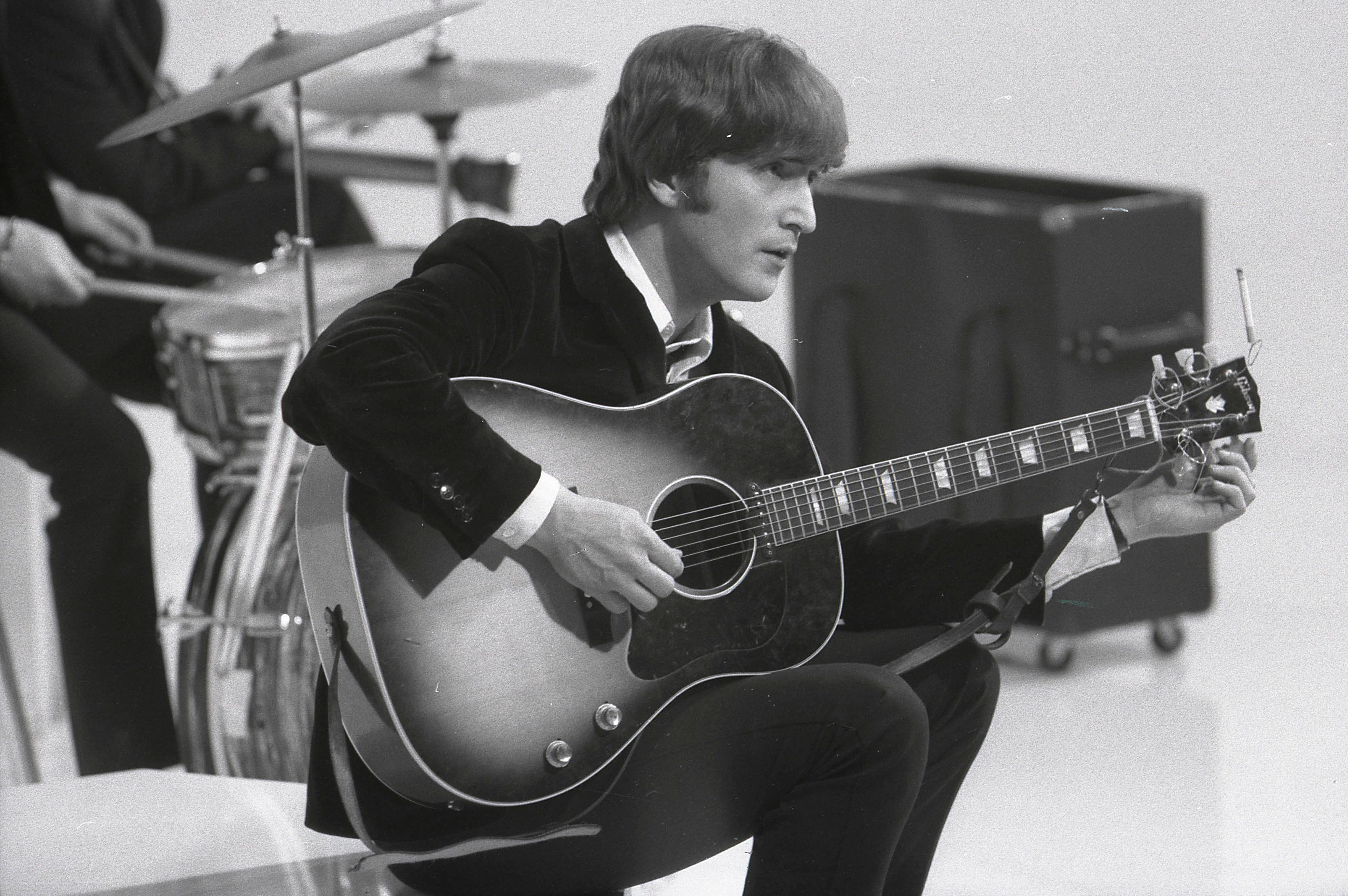 UNSPECIFIED - CIRCA 1960:  Photo of BEATLES and John LENNON; of the Beatles, tuning guitar (Gibson J160E acoustic) during the filming of 'A Hard Day's Night' at the Scala Theatre  (Photo by Max Scheler - K & K/Redferns)