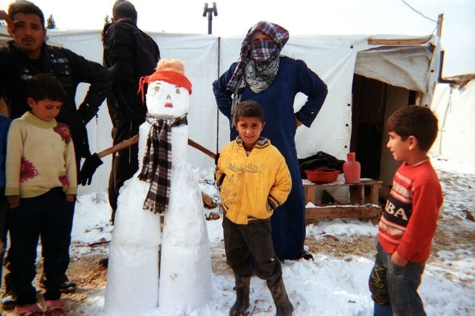 Shot by Akram, age 8, from Aleppo, Syria.<strong><br></strong> Children and adults stand next to a snowman they've made