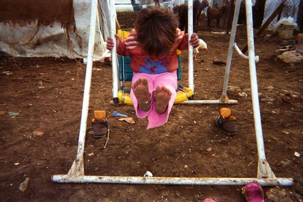 Shot by Gharam, age 12, from Homs Governorate, Syria.<strong><br></strong> A child plays on a swing in an informal settl