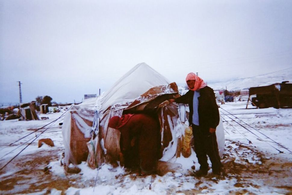 Shot by Ahmad, age 7, from Aleppo Governorate, Syria.<strong><br></strong> A woman and a man remove snow from the entran