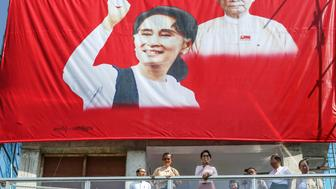 Aung San Suu Kyi, Myanmar's opposition leader and chairperson of the National League for Democracy (NLD), center right, delivers a speech flanked by Tin Oo, co-founder of the NLD, center left, from a balcony at the party headquarters in Yangon, Myanmar, on Monday, Nov. 9, 2015. Suu Kyi warned supporters anticipating an historic election victory over the military-backed ruling party that results are not final and they need to remain cautious. Photographer: Dario Pignatelli/Bloomberg via Getty Images