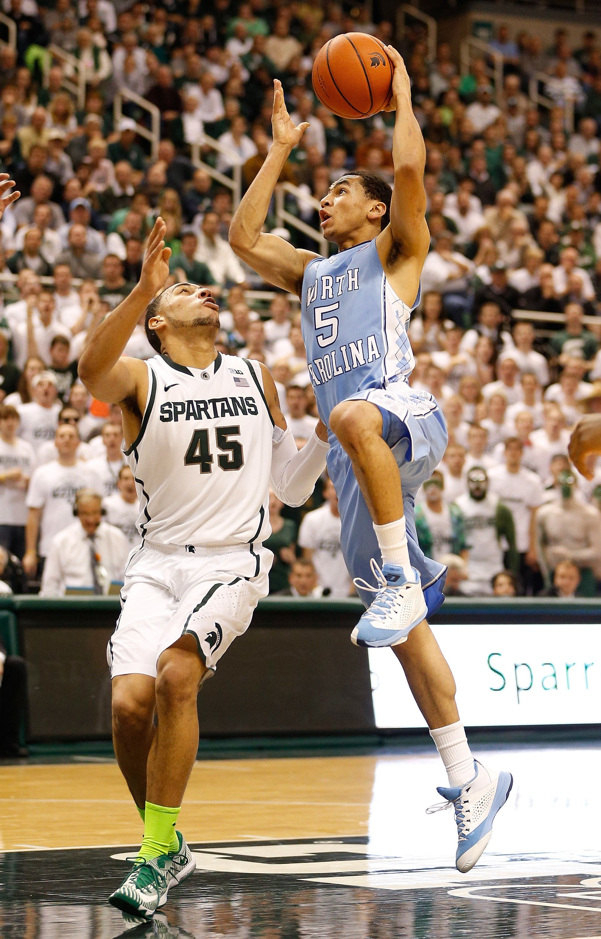 EAST LANSING, MI - DECEMBER 04:  Marcus Paige #5 of the North Carolina Tar Heels tries to get to the basket past Denzel Valentine #45 of the Michigan State Spartans during the first half at the Jack T. Breslin Student Events Center on December 4, 2013 in East Lansing, Michigan. (Photo by Gregory Shamus/Getty Images)