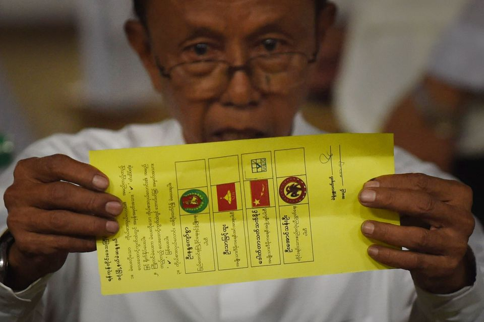 A poll official holds a ballot marked for Aung San Suu Kyi's opposition party National League for Democracy (NLD) in Myanmar
