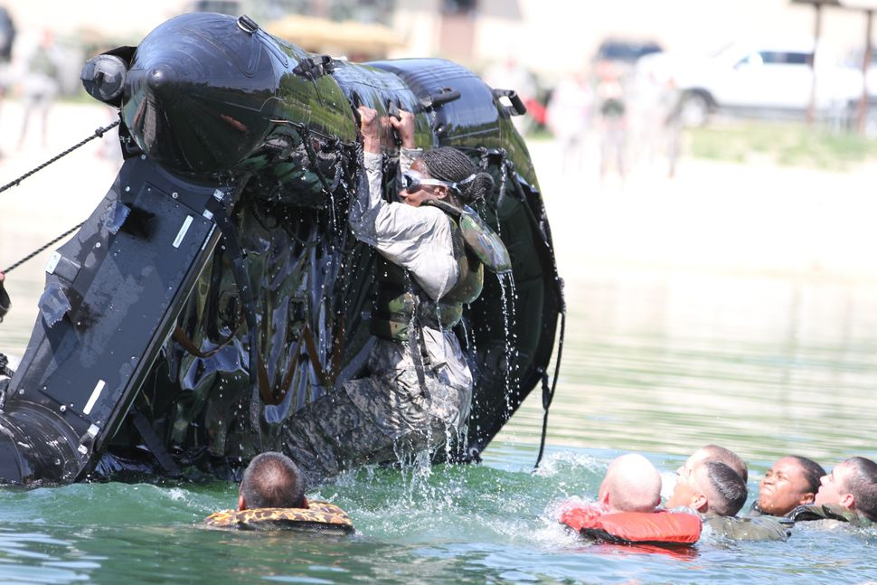Cpl. Denise Houston hangs on to a Zodiac boat as she, along with fellow soldiers, try to get the watercraft turned back over