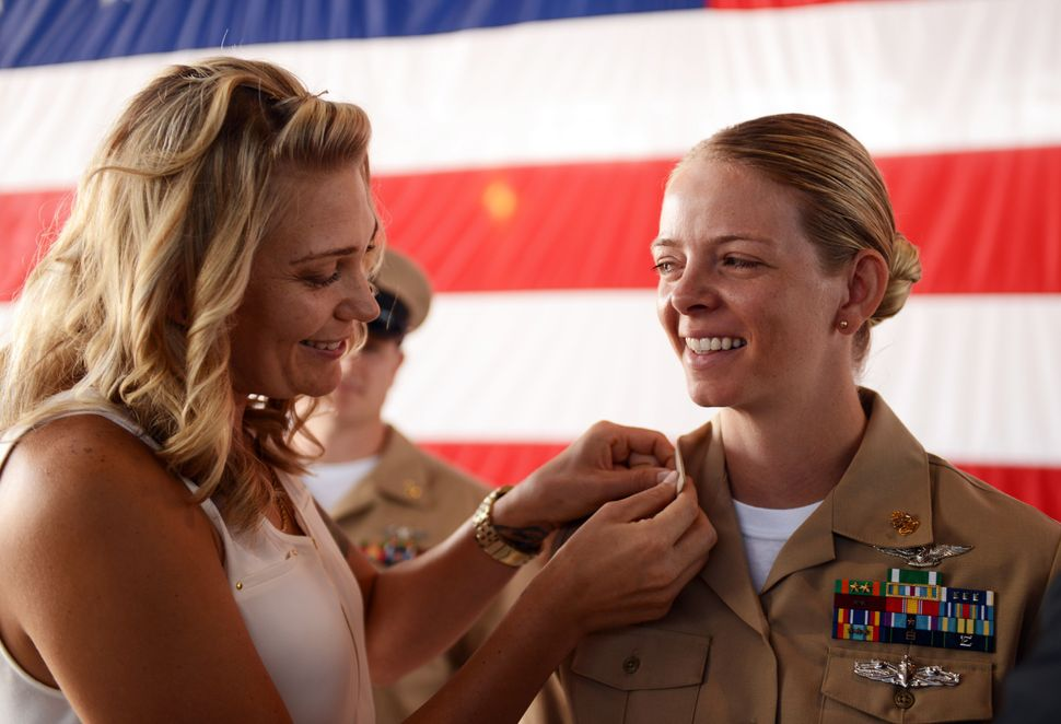 Chief Aviation Ordnanceman Misty Beck is pinned by her wife during a chief petty officer pinning ceremony at Naval Air Statio