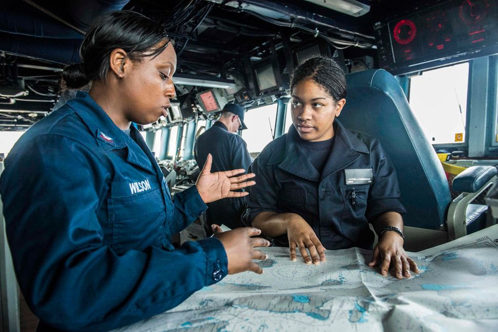 Quartermaster 2nd Class Nyzherelle Wilson (left) conducts training with Quartermaster Seaman Fayden Cunningham on the bridge