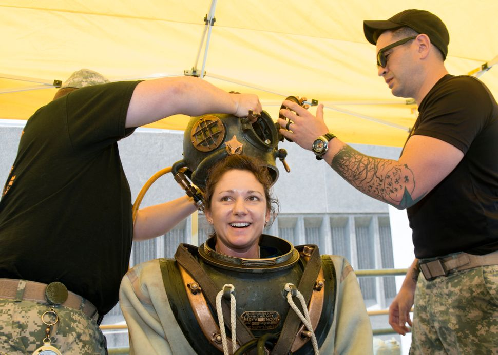 Sgt. Dagan Indeck assists Navy Diver 2nd Class Valerie De Freitas during a Mark V familiarization dive to commentate the Year
