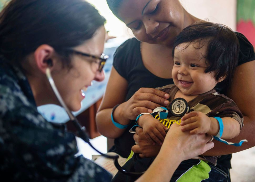 Lt Cmdr. Melissa Buryl, a pediatrician stationed at Naval Medical Center Portsmouth, VA, checks a child's vital signs at the
