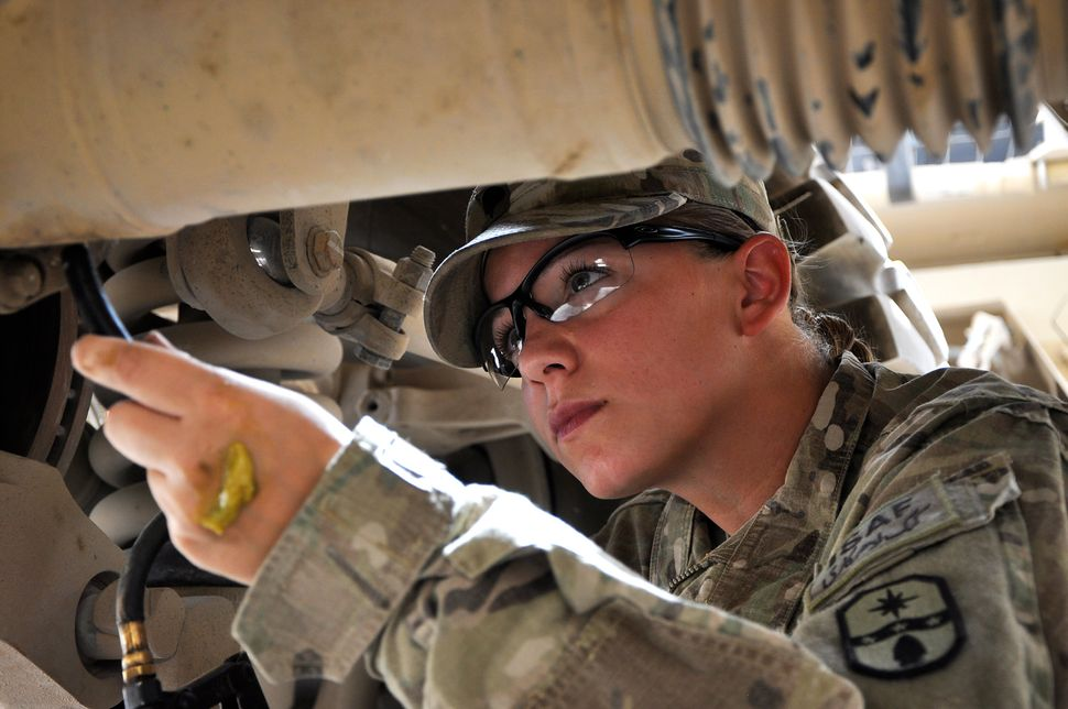 Spc. Michelle Metzger, a motor transport operator with 1487th Transportation Company, Ohio Army National Guard, applies greas