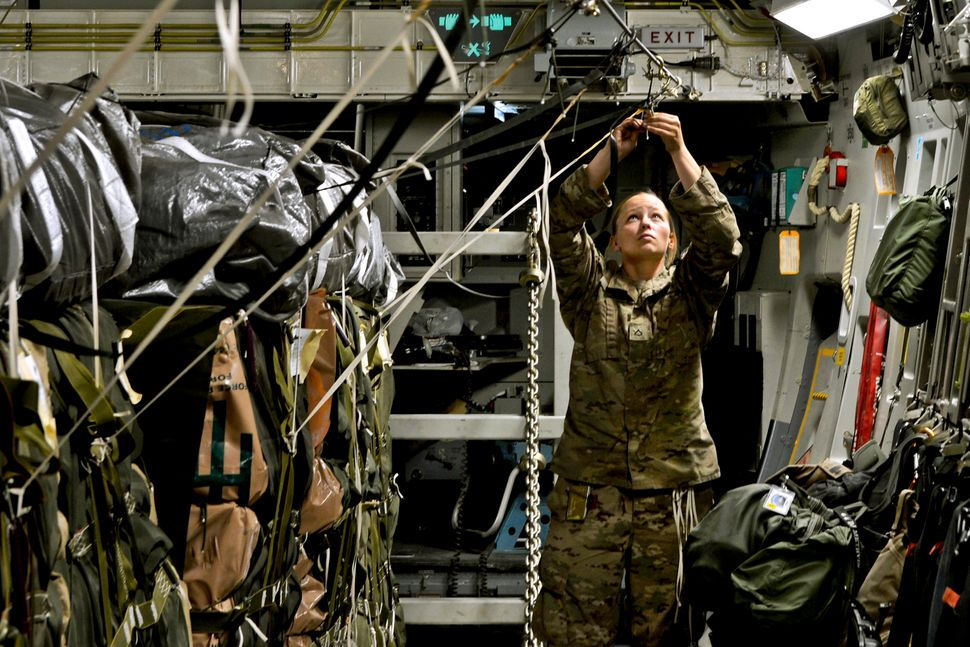 Private First Class Courtney Erwin secures an anchor cable to a C-17 assigned the 774th Expeditionary Airlift Squadron on Bag