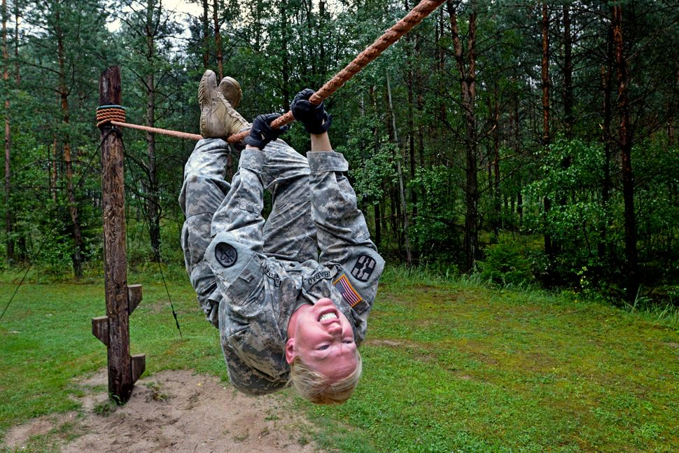 U.S. Army Spc. Elizabeth Ibabao goes across a rope bridge at the obstacle course during U.S. Army Europe's Best Warrior Compe