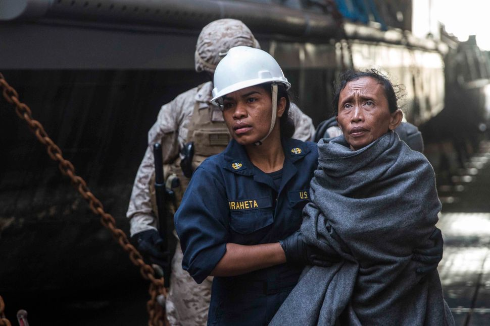 A Sailor takes a woman to medical staff aboard the amphibious dock landing ship USS Rushmore. Rushmore rescued 65 people from
