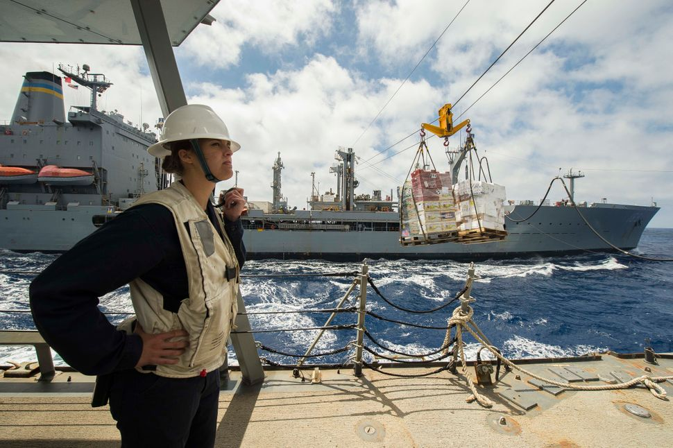 Ensign Danielle Garbarino monitors inbound supplies from the Military Sealift Command fleet replenishment oiler USNS John Len