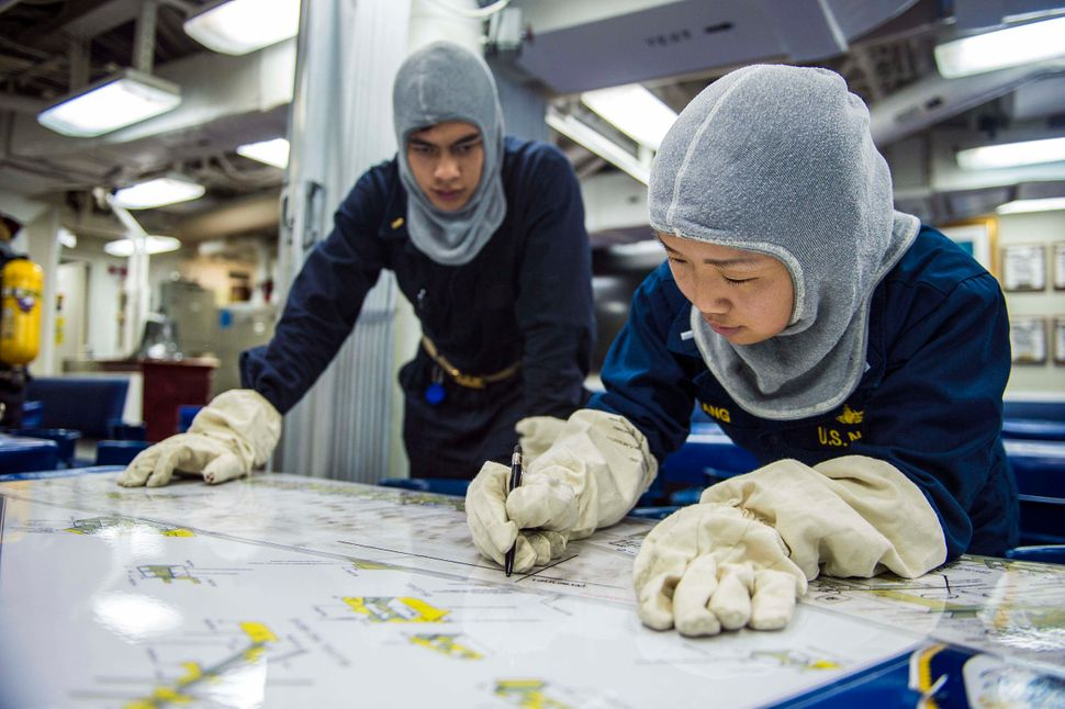 Lt. j.g Betty Chang, assigned to the Arleigh Burke-class guided-missile destroyer USS Mustin, plots casualty status on a char