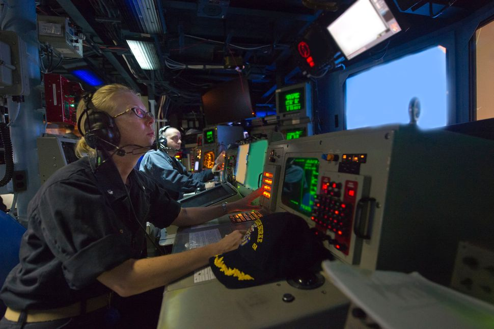 Cmdr. Camille Flaherty, commanding officer of the guided-missile destroyer USS Arleigh Burke, observes operations in the comb