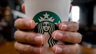 CHENGDU, SICHUAN PROVINCE, CHINA - 2015/09/11: Hand holding a cup of Starbucks coffee.  Starbucks is streamlining the ordering process so customers are able to get that cup of coffee  faster than usual. (Photo by Zhang Peng/LightRocket via Getty Images)