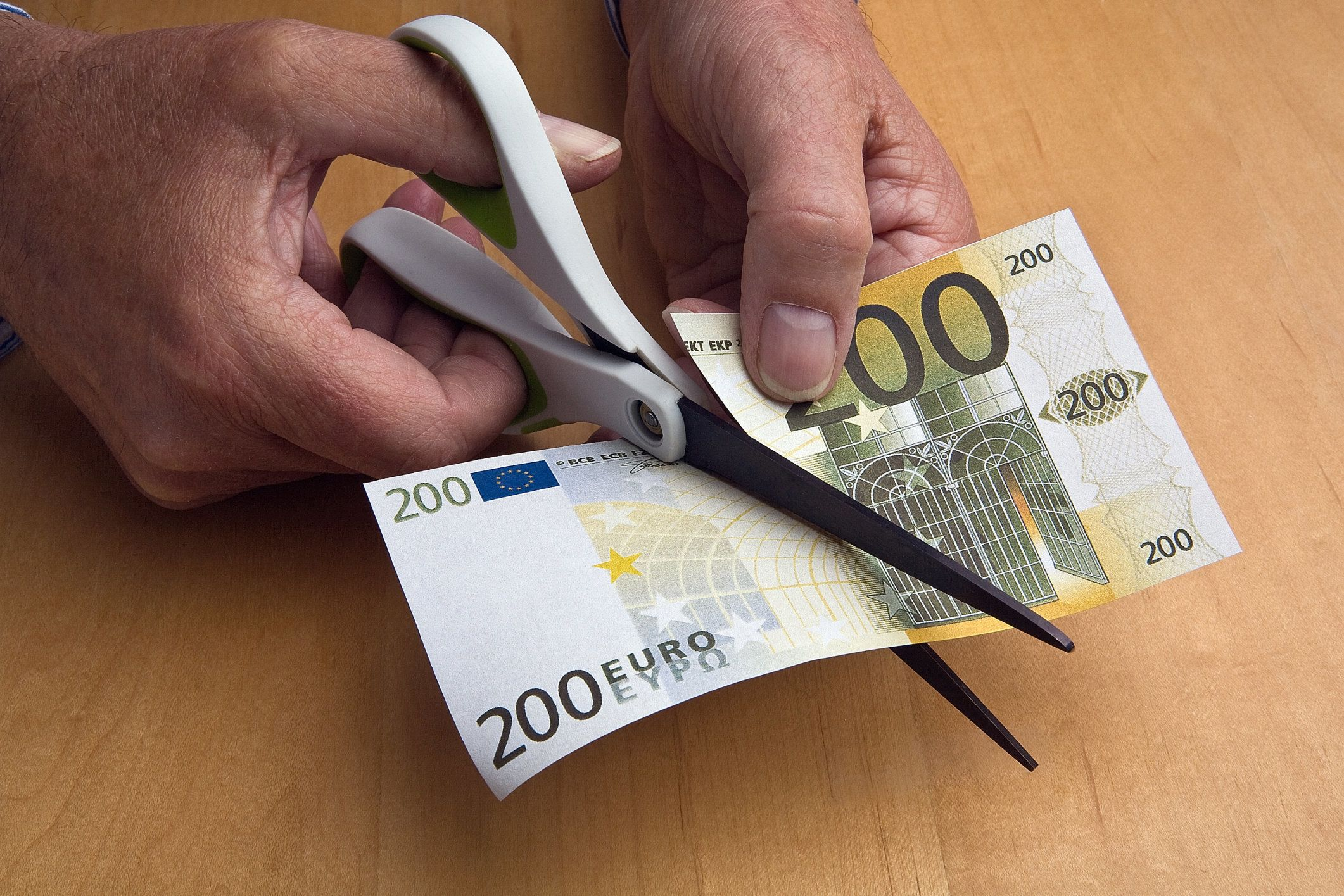 Scissors slice through euro banknote.
