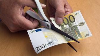 Scissors slice through euro banknote.